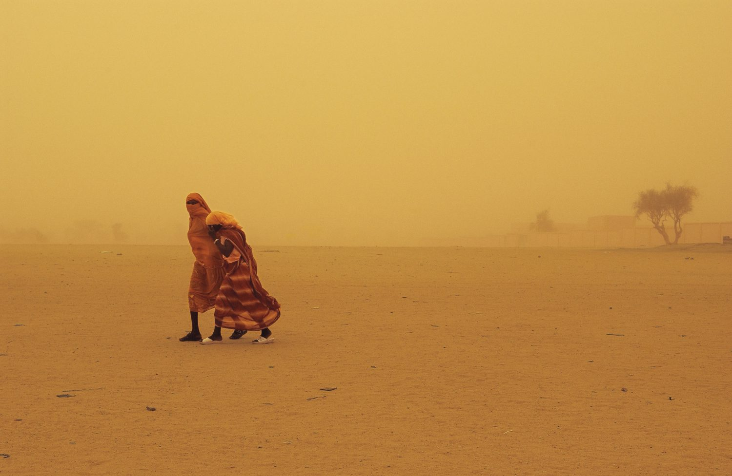 Two women walk through a sandstorm in Bahai, Chad, along the border with Darfur, Sudan, 