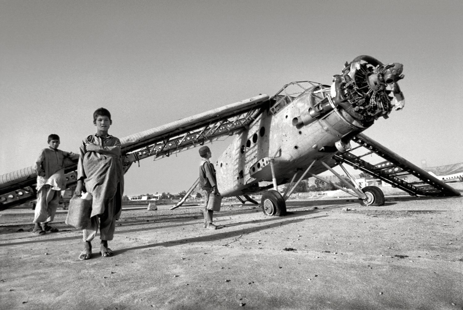 Boys play around a destroyed plane left over from the Soviet